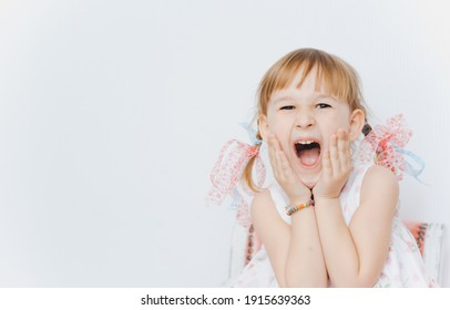 Portrait of a beautiful little emotional girl in a white dress with two pigtails and bows. Isolated over white background. Screaming child. Copy space.