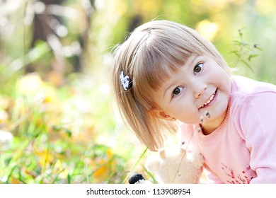 portrait of a beautiful little girl in the autumn forest