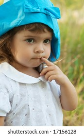 Portrait of a beautiful  little girl in blue hat with finger in mouth