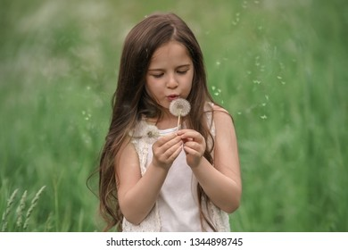 Portrait of a beautiful little girl with dandelions.