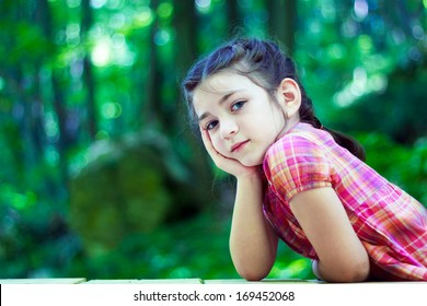 Portrait of a beautiful little girl in the forest. With hands on chin
