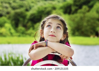 Portrait of a beautiful little girl with hands on chin looking up