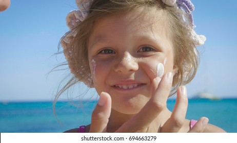 Portrait of beautiful little girl having fun on the sea, cute smiling in panama, sun protection cream, background of sea blue water. Concept: children, childhood, summer, freedom, kids, baby, summer.