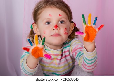 Portrait of a beautiful little girl with her ??hands in paint, ready to prints