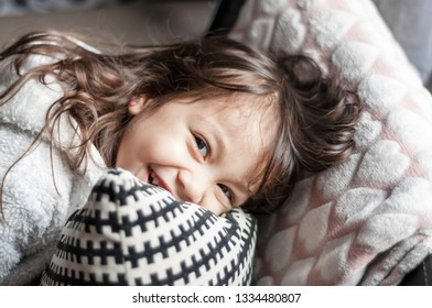 Portrait of beautiful little girl laughing on the couch