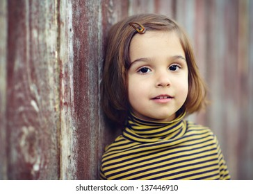 Portrait of a beautiful little girl leaning on a fence