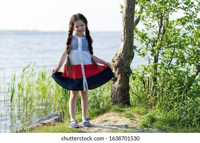 Portrait of a beautiful little girl with long hair near the lake on a sunny day.