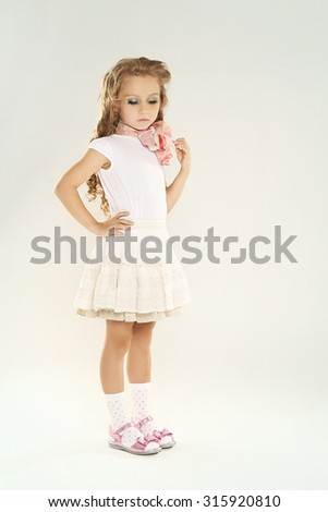 Portrait of a beautiful little girl with make-up, looks like a doll.