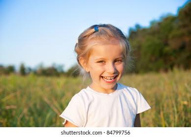 portrait of beautiful little girl in a meadow