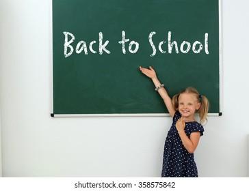 Portrait of beautiful little girl near chalkboard