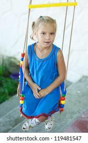 Portrait of beautiful little girl on swing in children's city park.