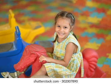 Portrait of a beautiful little girl on  rocking horse.