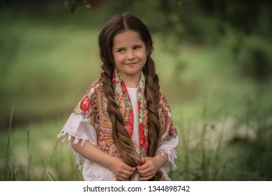 Portrait of a beautiful little girl with a scarf on her shoulders.