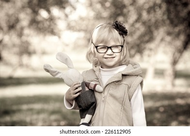 Portrait of  beautiful little girl wearing spectacles outdoors