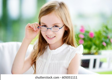 Portrait of beautiful little girl wearing glasses at home. Vision, health, ophthalmology concept.