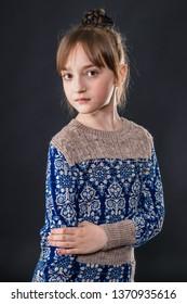 Portrait of a beautiful little schoolgirl on a dark background