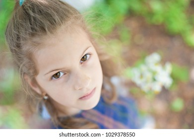 portrait of a beautiful little thoughtful girl looking at the camera