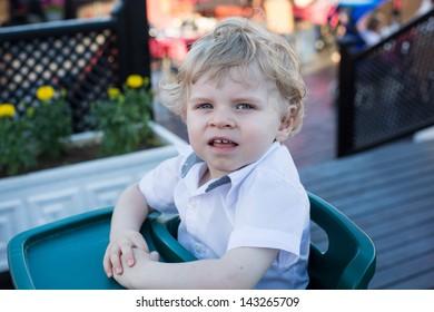 Portrait of beautiful little toddler boy sitting in outdoor restaurant in summer