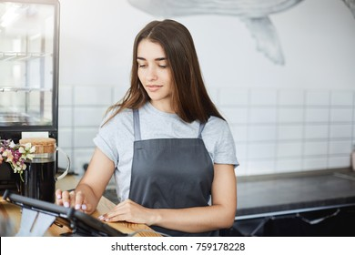 Portrait of beautiful long haired girl barista using a point of sale to run her successful coffee store business.