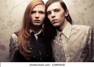 Portrait of beautiful long haired people in vintage style: handsome boy with brown hair and gorgeous red-haired girl posing together. Studio shot.