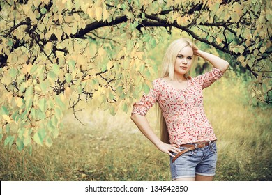 Portrait of a beautiful long-haired blonde girl in the autumn park. Perfect hair and make-up. Retro (80s) style. Outdoor shot
