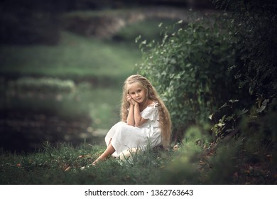 Portrait of a beautiful long-haired girl in the park. Image with selective focus and toning