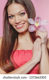 Portrait of a beautiful long-haired girl. Woman of mixed nationality. Orchids adorn the hair of a gorgeous brunette.