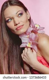 Portrait of a beautiful long-haired girl. Woman of mixed nationality. The brunette holds an orchid in her hands