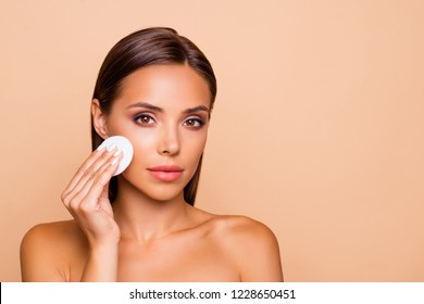 Portrait of beautiful lovely pretty  well-groomed charming lady with her naked shoulders she isolated on pastel beige background with copy space for text use micellar water and circle white pad