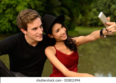 Portrait of beautiful loving couple using mobile phone to take picture of themselves in park