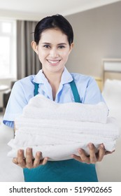 Portrait of beautiful maid carrying towels while smiling at the camera, shot in the hotel room