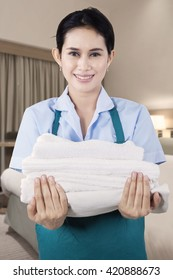 Portrait of a beautiful maid smiling at the camera while holding a pile of towels in the bedroom