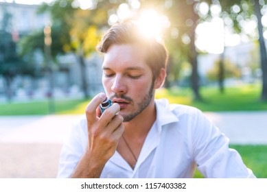 Portrait of beautiful man using asthma inhaler in park. Young man using inhaler during asthmatic attack at park. Man using a pressurized cartridge inhaler extended pharynx, Bronchodilator