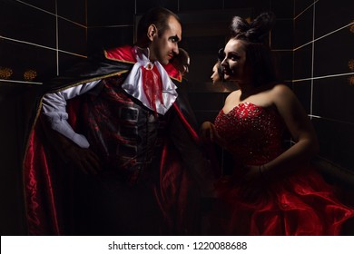 Portrait of Beautiful man and woman vampires dressed in medieval clothing stand in a restroom against mirrow.