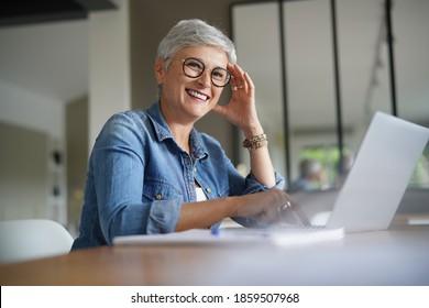 Portrait d'une belle femme mûre de 50 ans aux cheveux blancs travaillant à la maison