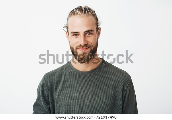 Portrait of beautiful mature blonde bearded guy with trendy hairdo in casual grey shirt smiling and looking in camera.