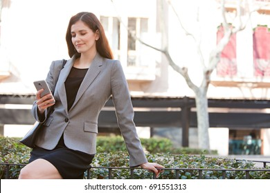 Portrait of beautiful mature business woman holding smart phone, financial city exterior, smiling. Professional female wearing smart clothes in sunny outdoors, using technology. Elegant working woman.