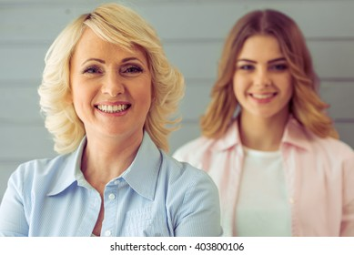Portrait of beautiful mature mother and her daughter looking at camera and smiling, standing one by one against gray background