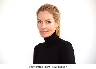 Portrait of beautiful mature woman with blond hair sitting at isolated white background.