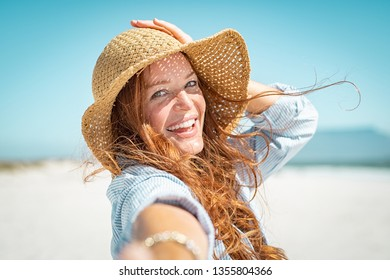Portrait of beautiful mature woman in casual wearing straw hat at seaside. Cheerful young woman smiling at beach during summer vacation. Happy girl with red hair and freckles enjoying the sun.