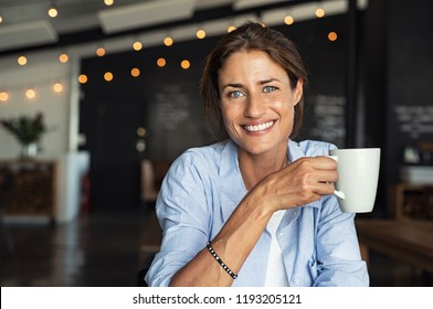 Portrait of beautiful mature woman drinking a cup of tea in cafeteria. Happy woman in a cafe drinking coffee and looking at camera. Portrait of smiling lady relaxing in a coffee shop.