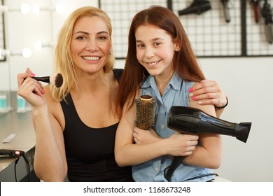 Portrait of a beautiful mature woman embracing her adorable little daughter posing with hairstyling equipment. Young girl holding blowdryer and a brush, smiling, posing with her mom
