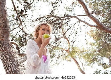 Portrait of beautiful mature woman in nature with trees biting a green apple on a sunny day, outdoors. Healthy senior woman eating fruit, wellness and well being lifestyle, smiling in sunny exterior.