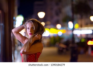 Portrait of a beautiful mature woman at night with the city lights in the background.