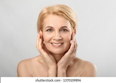 Portrait of beautiful mature woman on light background