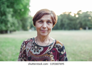 Portrait of beautiful mature woman in park at sunset during summer