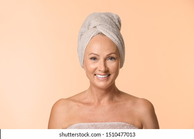 Portrait of beautiful mature woman with perfect skin on beige background