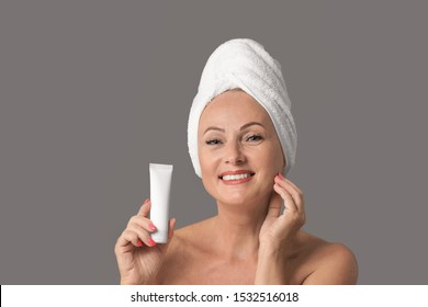 Portrait of beautiful mature woman with perfect skin holding tube of cream on grey background