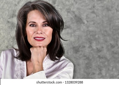 Portrait of a Beautiful Mature Woman Posing with Her Hand Under Her Chin Wearing a White Robe