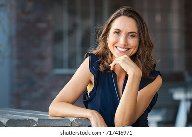 Portrait of beautiful mature woman sitting at coffee shop. Happy hispanic smiling woman sitting on a bench in outdoor cafeteria looking at camera. Portrait of carefree woman relaxing on bench.
